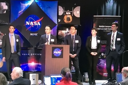 Javid Bayandor stands at podium at NASA event. At his side are student researchers.