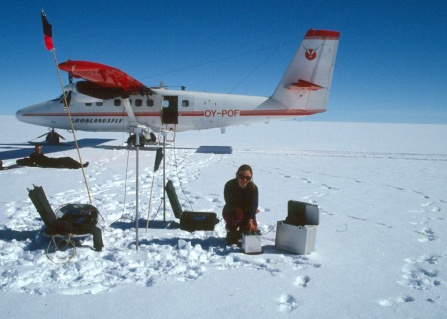 Beata Csatho on an icy landscape in front of a small plane.