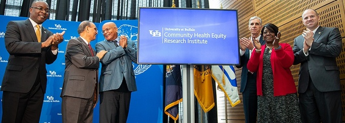"Photo of UB officials and elected leaders flanking a monitor that reads ""University at Buffalo Community Health Equity Research Institute.""."