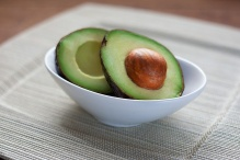 Two halves of an avocado in a white bowl.