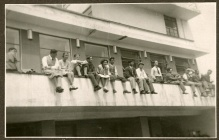 Black-and-white photo of people perched on a balustrade on the outside of a building.