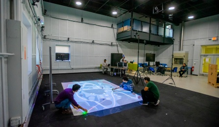 Wide view of engineering research lab, showing students setting up an experiment involving mini-drones, high-speed cameras and computers.