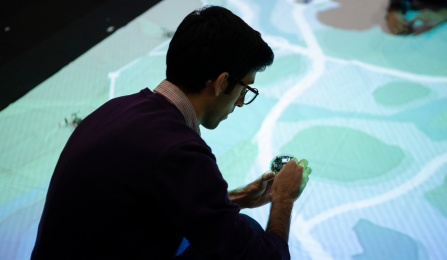 UB student works with mini-autonomous robot in front of a projected simulation of a city.