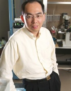 Jian Feng is standing in his lab.