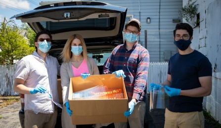 (l to r) Jordan Levine, Brittany Russo, Mitch Eyerman and Joshua Broden hold a box of face shields they made before loading it into a car.