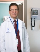 Gómez-Duarte in white coat, standing in patient exam room.