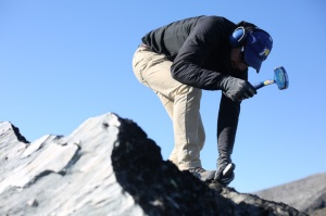 Scientist Nicolás Young perches atop a large boulder to chisel a sample from it.