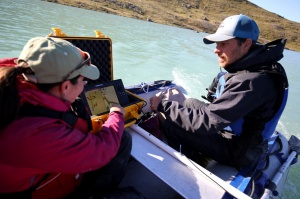 Scientists Jason Briner and Heidi Roop in Greenland, aboard a boat or pontoon.