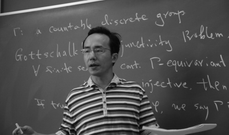 Hanfeng Li standing in front of a chalk board.