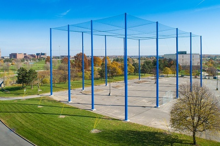 Large netted complex for drone use sits on concrete pad with UB North Campus in the background. Blue skies and colorful autumn trees.