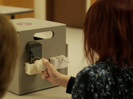 An mRehab study participant turns the 3D-printed doorknob.