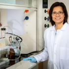 Chemistry professor Diana Aga in the lab, wearing a white lab coat and blue gloves next to a laboratory hood.
