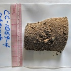 A half-cylinder-shaped sample of dirt sitting atop a plastic bag, labeled with a sample ID number in blue marker.