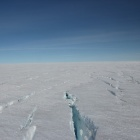 Large cracks on the surface of the Greenland Ice Sheet, a large white expanse.