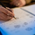 A hand uses a fountain pen to draw science-themed scribbles on a white page.