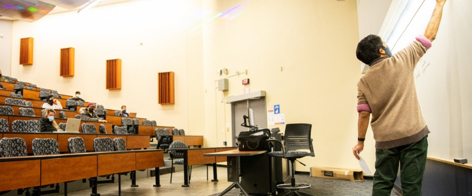 Photo of an instructor at the front of the lecture hall.