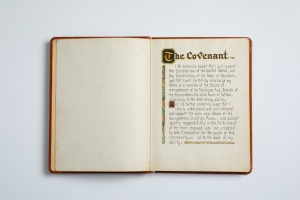 """A book opened to a page with decorative text stating, """"The Covenant,"""" and continuing to say that the people signing swear to faithfully carry out their duties."""