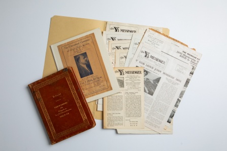 An open folder holding records of the Michigan Avenue Y.M.C.A. These include a leather-bound book that is reddish brown in hue, as well as a variety of papers, some of which have begun to yellow.