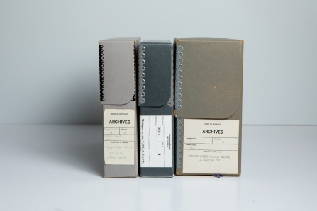 Three archival boxes in different shades of gray, of different sizes, holding part of the archives of the Michigan Avenue Y.M.C.A.
