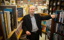 Michel Bruneau standing among the bookshelves at Talking Leaves bookstore.