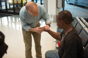 UB physician Christian DeFazio examines a homeless man's hand at the bus station.