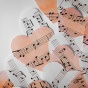 pink and white paper hearts cut out of sheet music