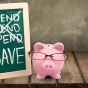 "Photoillustration of the concept of saving featuring a piggybank wearing glasses and a chalkboard with the words ""spend, spend, spend"" crossed out and ""save"" written below"