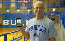 Michael May on track in Alumni Arena with a smartphone showing a photo of his 80-pound-heavier self.