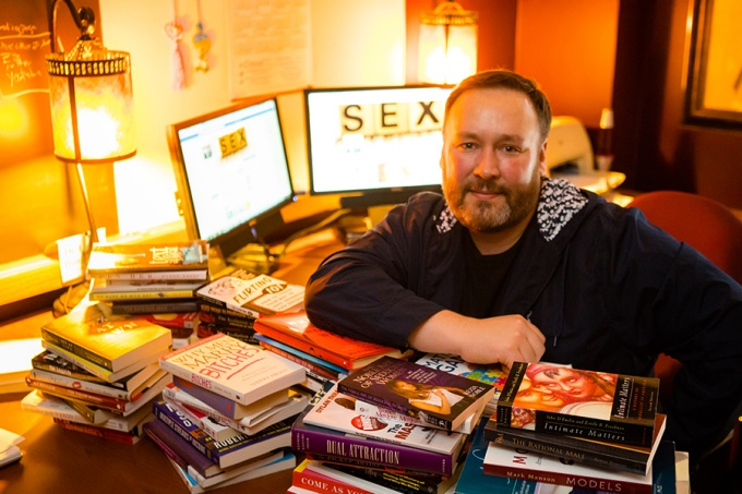 Lance Rintamaki in his office, books strewn across his desk, the word SEX visible on a computer behind him.