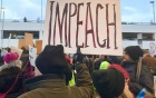 "Protester holds up a sign that says ""Impeach"" at an emergency protest against Muslim ban at Detroit Metropolitan Wayne County Airport's McNamara Terminal on 29 January 2017."