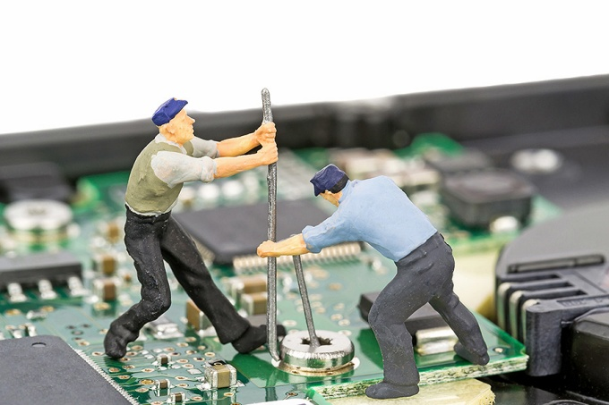 Photo illustration featuring miniature figurines repairing an electronic device