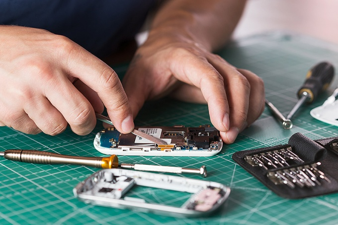 Close up of man's hands while repairing an electronic device