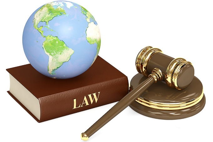 Photograph of a globe on top of a law book, next to a judge's gavel. Environmental law concept