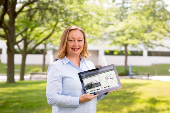 Geocove CEO Karyn Tareen standing outside UB Technology Incubaor holding a computer tablet