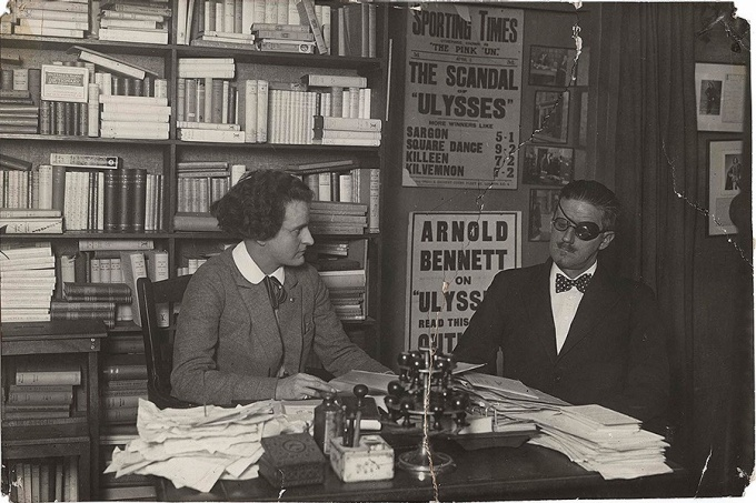 James Joyce seated at a table with Sylvia Beach
