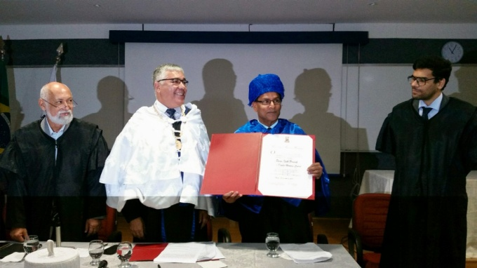 Paras Prasad holds the honorary doctorate he received from the Federal University of Pernambuco (UFPE) in Brazil. To his left is Anisio Brasileiro, rector of UFPE.