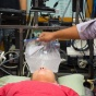 A researcher holds a plastic bag filled with ice water slurry over a person's forehead, eyes and cheeks.