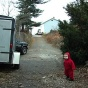 Still from video The Distance I can Be From My Son (Back Alley). toddler in a red suit heading down an alley