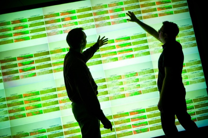 silhouettes of two men standing before screen of big data