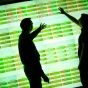 Silhouettes of two men pointing to a screen of big data.