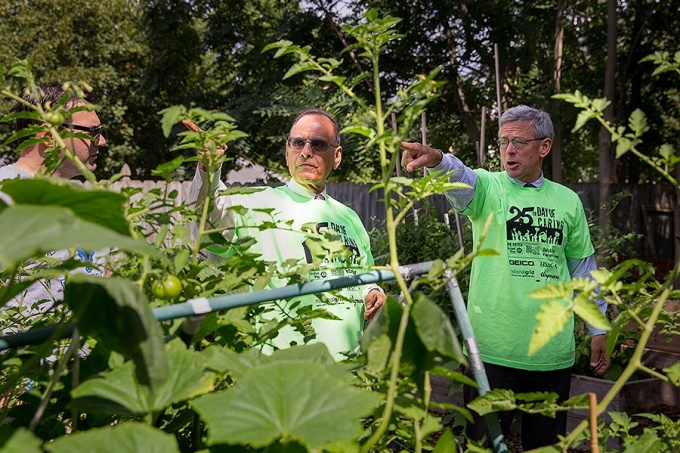 President Tripathi and Provoost Zukoski discuss the irrigation system at the Tyler Street Community Garden near UB's South Campus.