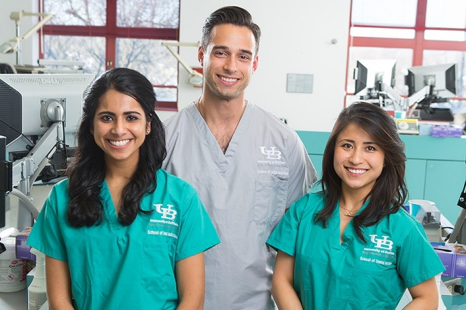 three smiling dental students