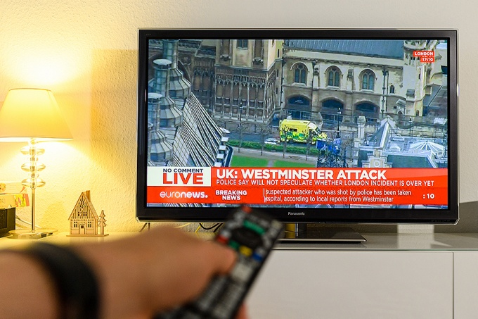 TV screen featuring news coverage of a violent event