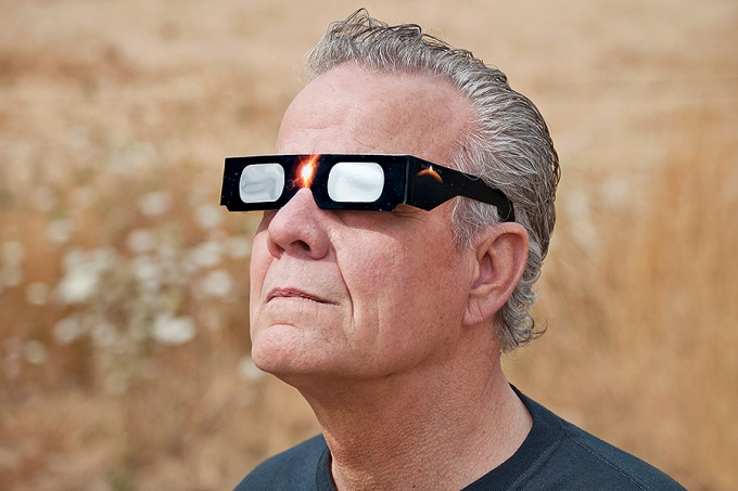 Man wearing eclipse glasses to look at eclipse