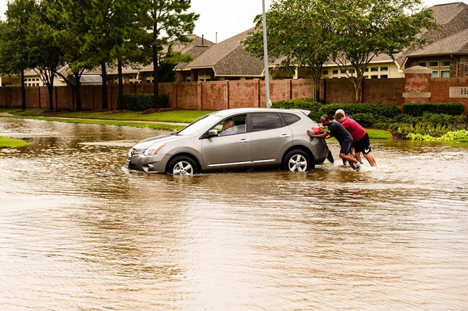 Neighbors help push a stranded motorist through flood waters