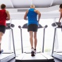 View from the back of 3 mature men running on a treadmill