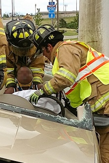 Lt. Will (?) helps in the extrication of a driver involved in a car accident on the UB North campus.