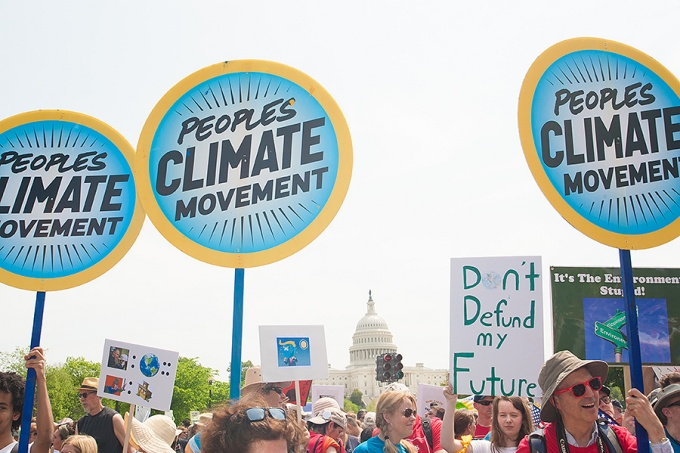 Protesters hold signs at Peoples Climate March, which backed action on climate change, in Washington DC on April 29, 2017