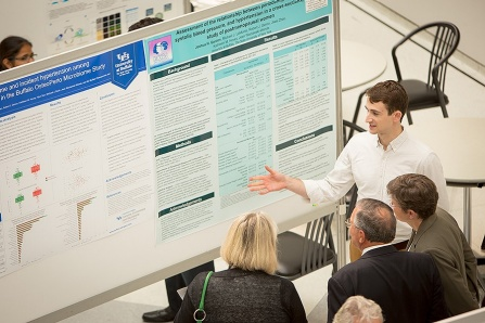 Josh Gordon discusses his poster and research at the Communities of Excellence, year 2 Program review, Conference poster presenation in the Center for the Arts atrium.