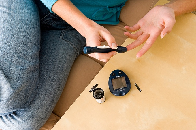 Diabetic person using a glucometer